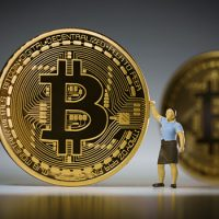 BERLIN, GERMANY - FEBRUARY 15:  In this photo illustration miniature figures standing beside model Bitcoins on February 15, 2016 in Berlin, Germany. (Photo Illustration by Thomas Trutschel/Photothek via Getty Images)